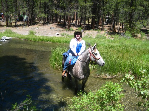 Nancy Brown riding Pax on a horseback riding vacation at McKay Crossing Campground in La Pine, Oregon