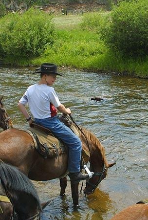 Taking a water break during a horseback riding vacation at Tarryall River Ranch