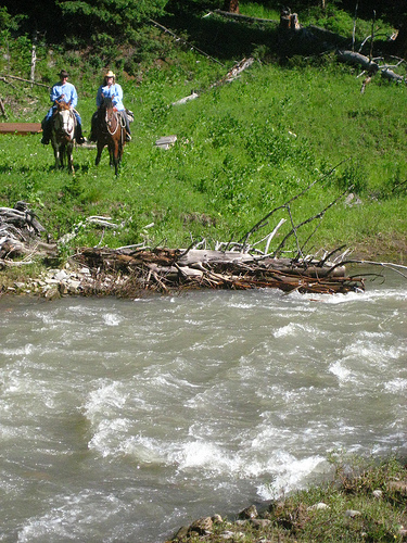 Dean Genge and Nancy Brown ride horseback along a Gallatin River tributary at the Club at Spanish Peaks in Big Sky, Montana