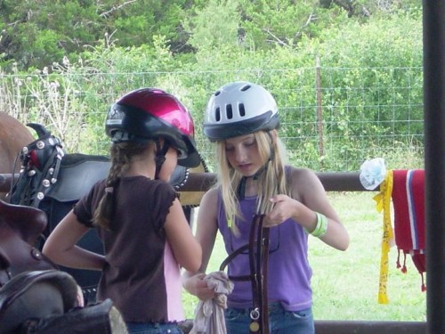 Young cowgirls learn how to clean tack at Sugar & Spice Ranch in Bandera, Texas