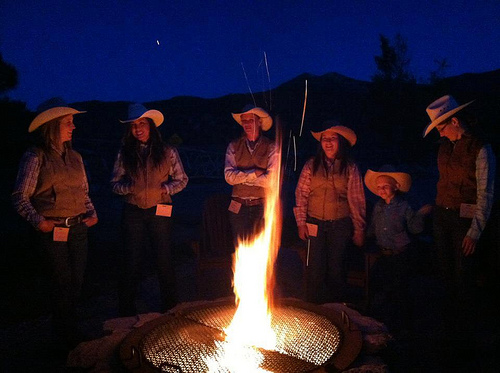 High Lonesome Ranch wranglers gather round the campfire after a horseback riding vacation in De Beque, Colorado