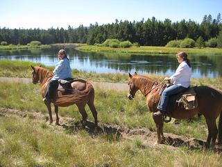 Nancy riding Fargo and Shelley riding Sally on a horseback riding vacation along the Deschutes river.